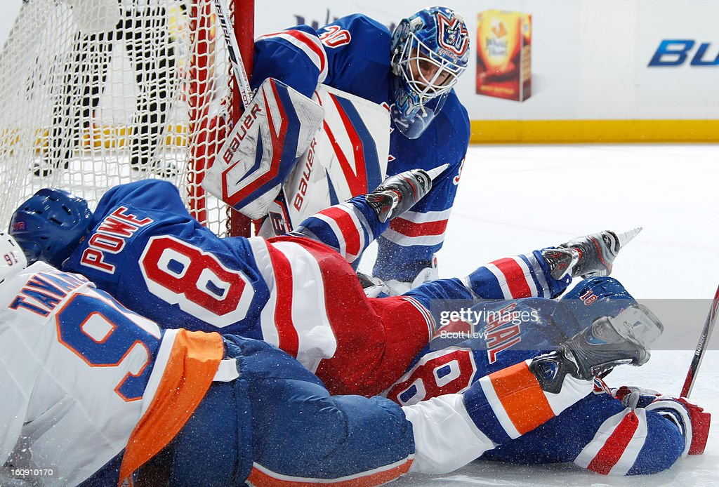 Darroll Powe #8 and Marc Staal #18 of the New York Rangers protect the net against John Tavares #91 of the New York Islanders at Madison Square Garden on February 7, 2013 in New York City.