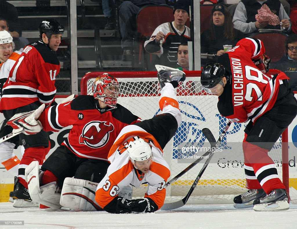 Darroll Powe #36 of the Philadelphia Flyers is upended as goaltender Johan Hedberg #1 and Anton Volchenkov #28 of the New Jersey Devils defend the net at the Prudential Center on November 27, 2010 in Newark, New Jersey.