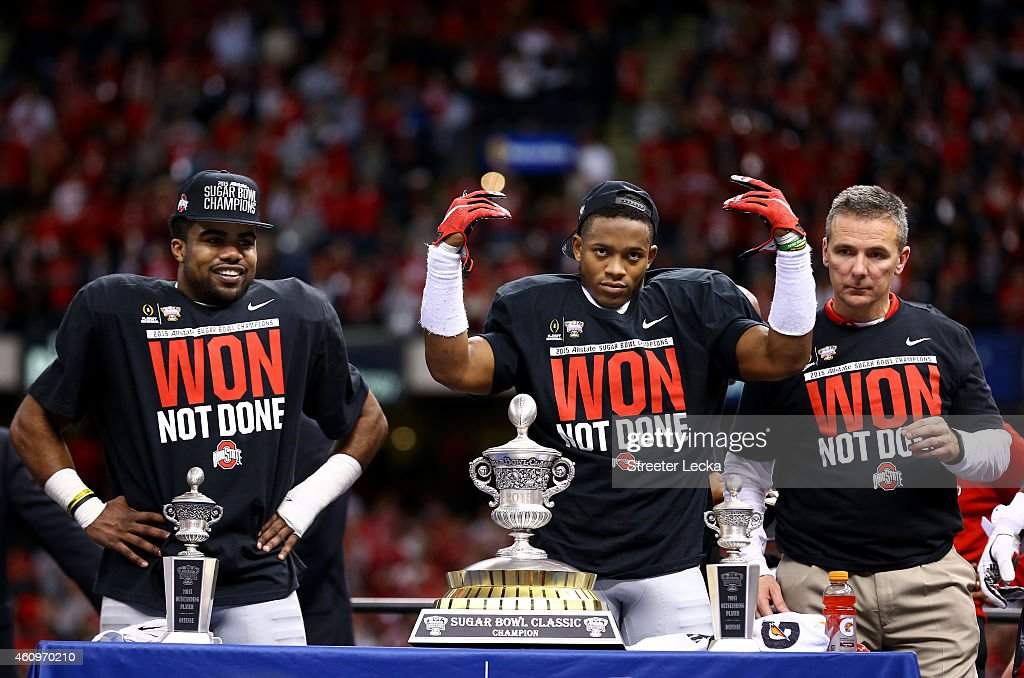 Darron Lee (C) #43 and Ezekiel Elliott (L) #15 and head coach Urban Meyer (R) of the Ohio State Buckeyes celebrate with the trophy after defeating the Alabama Crimson Tide in the All State Sugar Bowl at the Mercedes-Benz Superdome on January 1, 2015 in New Orleans, Louisiana. The Ohio State Buckeyes defeated the Alabama Crimson Tide 42 to 35.
