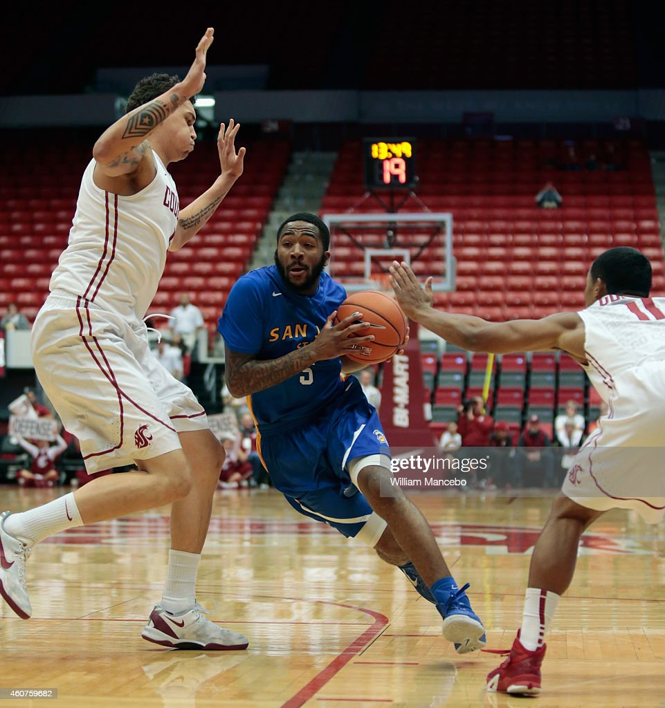Darryl Gaynor of the San Jose State Spartans drives to the basket between Jordan Railey and Trevor Dunbar of the Washington State Cougars in the...