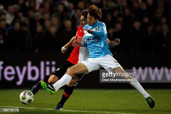 Darryl Janmaat of Feyenoord is tackled by Yuki Otsu of Venlo during the Eredivisie match between Feyenoord and VVV Venlo at De Kuip on April 5 2013...