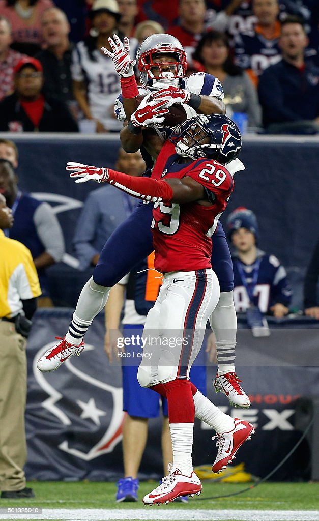 Darryl Roberts #28 of the New England Patriots jumps over Andre Hal #29 of the Houston Texans but is unable to hold on to the ball at NRG Stadium on December 13, 2015 in Houston, Texas.
