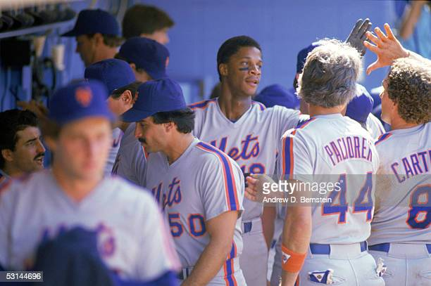 Darryl Strawberry of the New York Mets gets highfives by his teammates in the dugout during a game circa 19831990