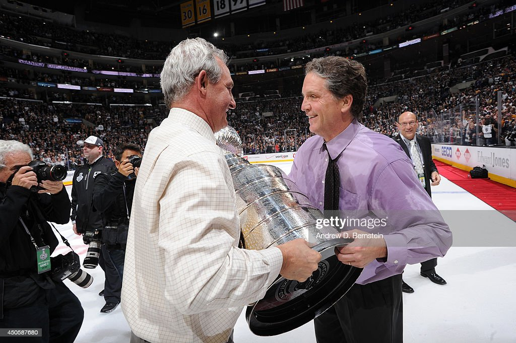 Darryl Sutter of the Los Angeles Kings hands the Stanley Cup Trophy over to general manager Dean Lombardi after defeating the New York Rangers in the second overtime period of Game Five of the 2014 NHL Stanley Cup Final at Staples Center on June 13, 2014 in Los Angeles, California.
