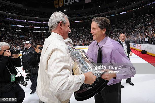 Darryl Sutter of the Los Angeles Kings hands the Stanley Cup Trophy over to general manager Dean Lombardi after defeating the New York Rangers in the...