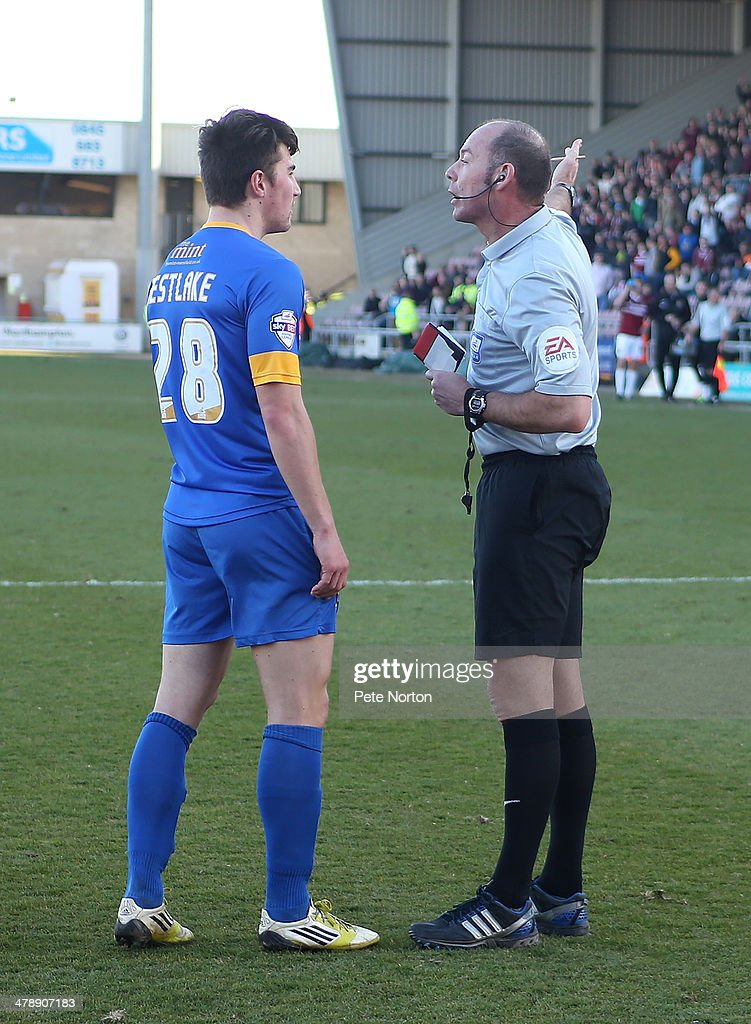 Darryl Westlake of Mansfield Town is sent off by referee Andy Haines after handling the ball to concede a penalty during the Sky Bet League Two match between Northampton Town and Mansfield Town at Sixfields Stadium on March 15, 2014 in Northampton, England.