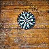 Dart board on a wooden grunge plank wall