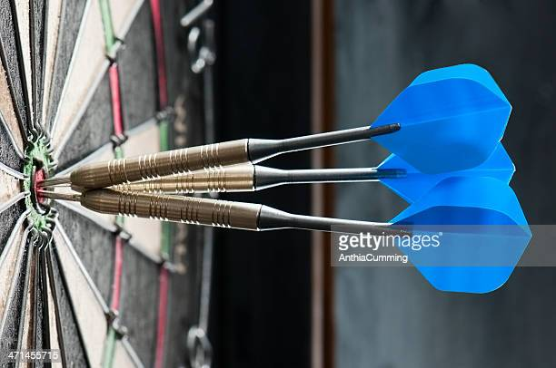 Dart board with three darts in the bulls eye