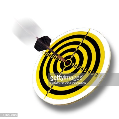 Dart flying into bull's eye of dartboard, close-up