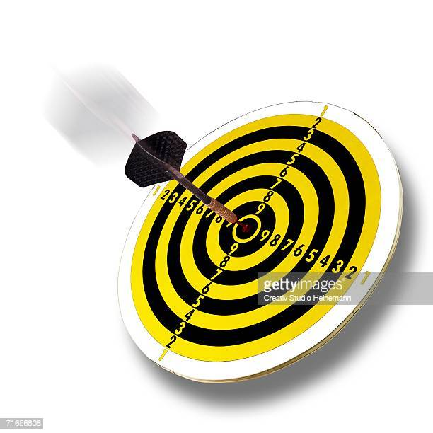Dart flying into bull's eye of dartboard, close-up