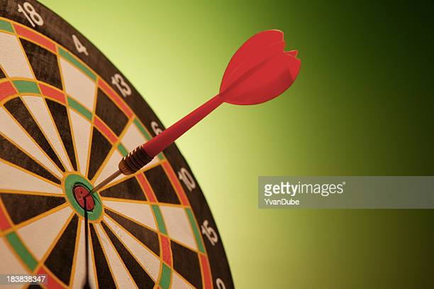 dart in bulls-eye dartboard