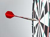 Dart in bullseye of dart board, side view, close-up