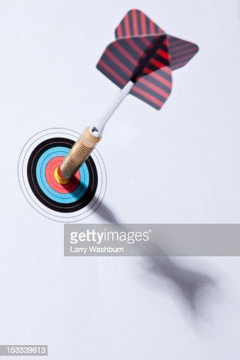A dart stuck in the bull's eye of a miniature archery target