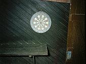 Dartboard on wooden panelled wall by open door