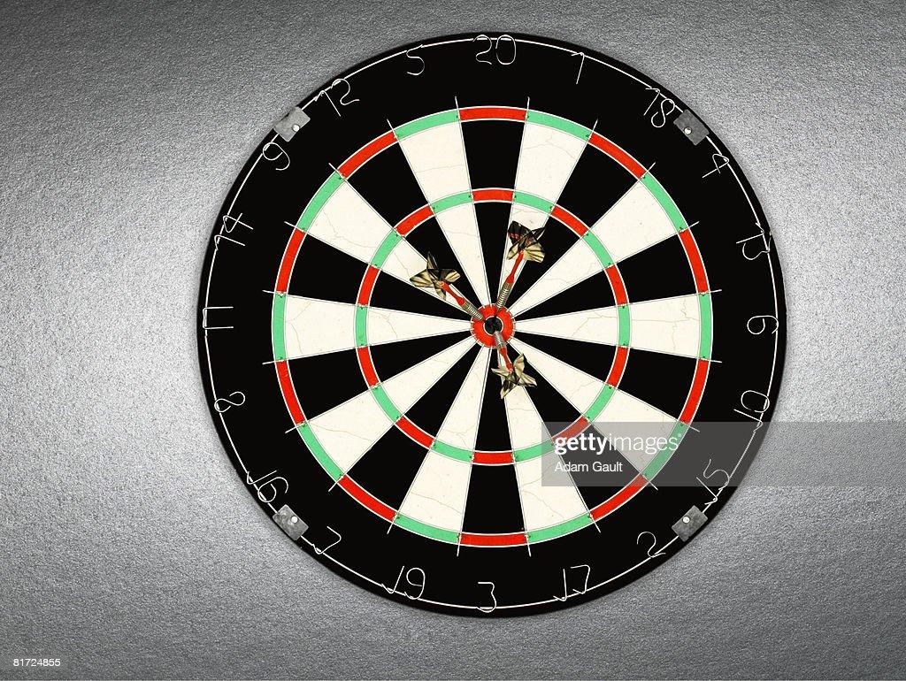 A dartboard with three darts in bullseye : Stock Photo