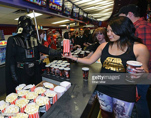 Darth Vader cosplayer from The Twin Suns Star Wars Club serves popcorn to fans on opening night of Walt Disney Pictures And Lucasfilm's 'Star Wars...