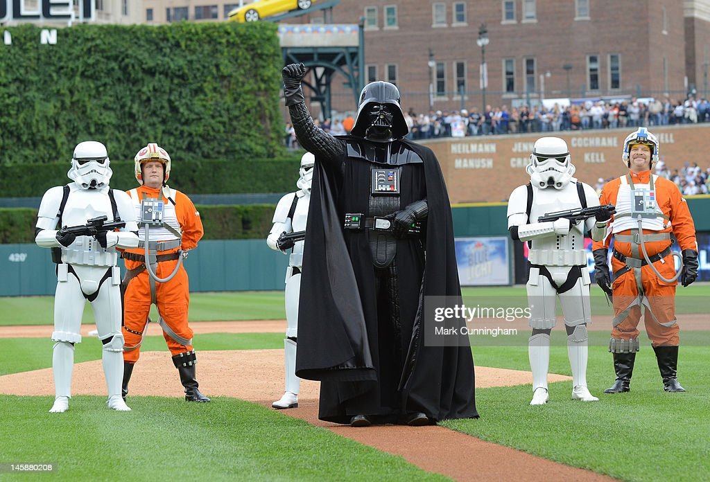 Darth Vader waves to the crowd after throwing out the ceremonial first pitch while surrounded by other characters during Star Wars Night before the game between the Detroit Tigers and the New York Yankees at Comerica Park on June 2, 2012 in Detroit, Michigan. The Tigers defeated the Yankees 4-3.