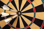 Darts in bull's eye on dartboard