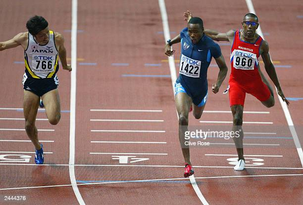 Darvis Patton of USA crosses the finish line next to Shingo Suetsugu of Japan and Stephane Buckland of Maritius during the men's 200m final at the...