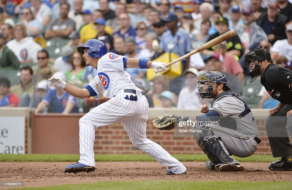 Darwin Barney #15 of the Chicago Cubs (L) follows through on an RBI single scoring teammates Starlin Castro #13 and Anthony Rizzo #44 as Jonathan Lucroy #20 of the Milwaukee Brewers catches during the fifth inning at Wrigley Field on July 30, 2013 in Chicago, Illinois.