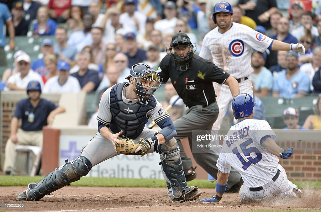 <a gi-track='captionPersonalityLinkClicked' href=/galleries/search?phrase=Darwin+Barney&family=editorial&specificpeople=537975 ng-click='$event.stopPropagation()'>Darwin Barney</a> #15 of the Chicago Cubs (R) scores past catcher <a gi-track='captionPersonalityLinkClicked' href=/galleries/search?phrase=Jonathan+Lucroy&family=editorial&specificpeople=5732413 ng-click='$event.stopPropagation()'>Jonathan Lucroy</a> #20 of the Milwaukee Brewerson an RBI single hit by Carlos Villanueva #33 during the fifth inning at Wrigley Field on July 30, 2013 in Chicago, Illinois.
