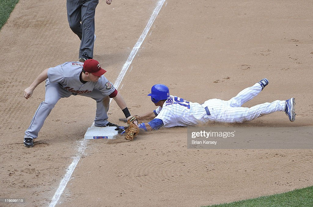 Darwin Barney of the Chicago Cubs slides safely into third base with a steal as third baseman Chris Johnson of the Houston Astros applies a late tag...