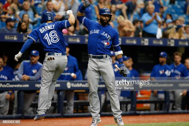 Darwin Barney of the Toronto Blue Jays celebrates with Jose Bautista as he heads for the dugout following his home run off of pitcher Alex Cobb of...