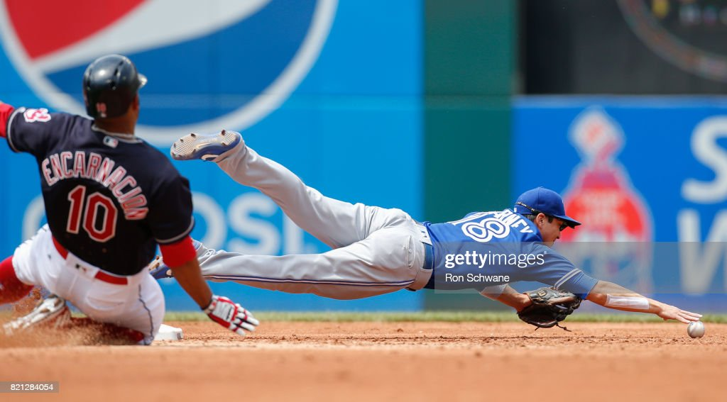 Darwin Barney #18 of the Toronto Blue Jays dives for a ball on a throwing error by Josh Donaldson allowing Edwin Encarnacion #10 of the Cleveland Indians to be safe at second base during the third inning at Progressive Field on July 23, 2017 in Cleveland, Ohio.