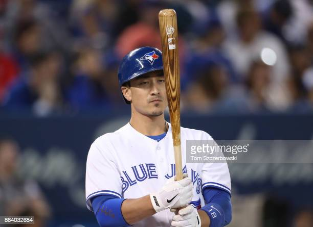 Darwin Barney of the Toronto Blue Jays inspects his bat as he bats in the eighth inning during MLB game action against the Boston Red Sox at Rogers...