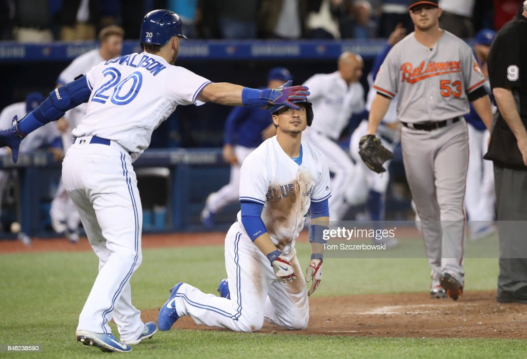 Darwin Barney #18 of the Toronto Blue Jays is congratulated by Josh Donaldson #20 after scoring on the game-winning run on an RBI single by Richard Urena #7 in the ninth inning during MLB game action against the Baltimore Orioles at Rogers Centre on September 12, 2017 in Toronto, Canada.
