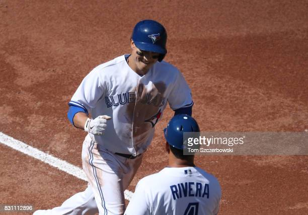 Darwin Barney of the Toronto Blue Jays is congratulated by third base coach Luis Rivera as he circles the bases after hitting a solo home run in the...