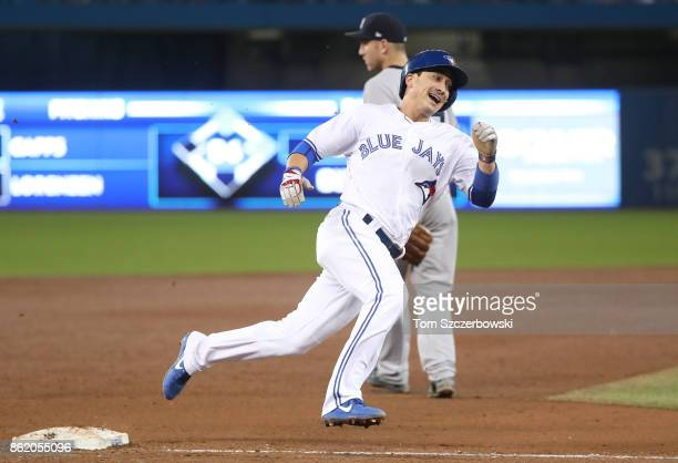 Darwin Barney of the Toronto Blue Jays rounds third base and runs home to score a run on an RBI double by Ryan Goins in the sixth inning during MLB...