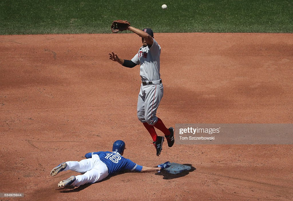 <a gi-track='captionPersonalityLinkClicked' href=/galleries/search?phrase=Darwin+Barney&family=editorial&specificpeople=537975 ng-click='$event.stopPropagation()'>Darwin Barney</a> #18 of the Toronto Blue Jays slides back safely to second base on a pick-off attempt thrown over the head of <a gi-track='captionPersonalityLinkClicked' href=/galleries/search?phrase=Xander+Bogaerts&family=editorial&specificpeople=9461957 ng-click='$event.stopPropagation()'>Xander Bogaerts</a> #2 of the Boston Red Sox jumps for the high throw in the third inning during MLB game action on May 28, 2016 at Rogers Centre in Toronto, Ontario, Canada.