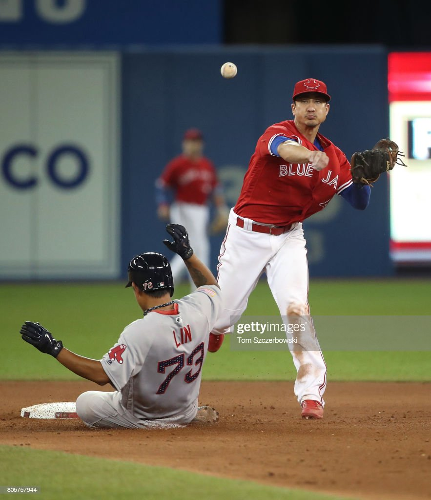 Darwin Barney #18 of the Toronto Blue Jays turns a double play in the eighth inning during MLB game action as Tzu-Wei Lin #73 of the Boston Red Sox slides into second base at Rogers Centre on July 2, 2017 in Toronto, Canada.