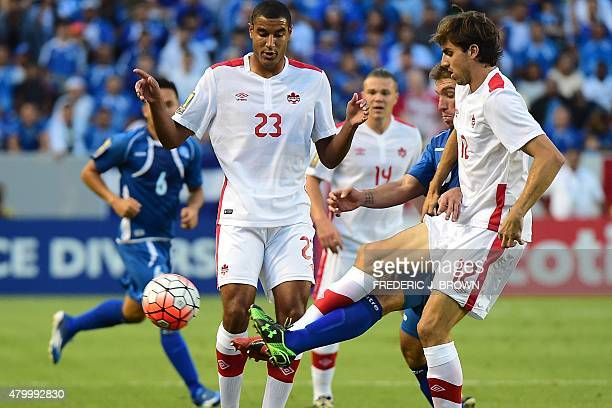 Darwin Ceren of El Salvador vies for the ball with Dejan Jakovic of Canada as Tesho Akindele looks on during their 2015 Concacaf Gold Cup match in...