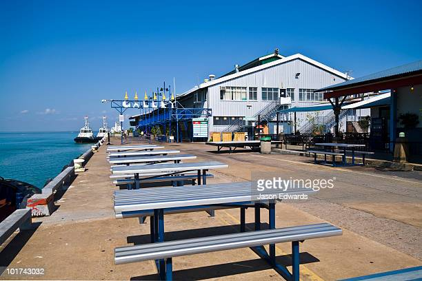 Picnic tables line a marina where tourists dine and and relax.