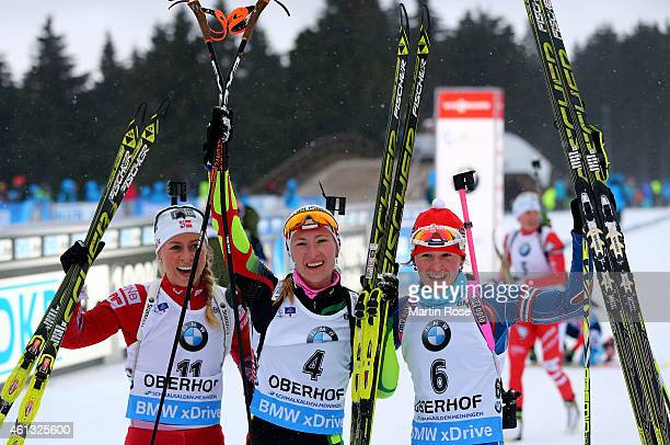 Darya Domracheva of Belarus celebrate with Tiril Eckhoff of Norway and Veronika Vitkova of Czech Republic after crossing the finish line during the...