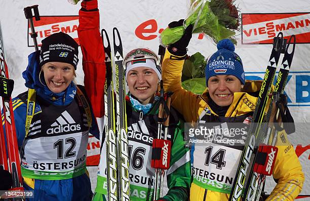 Darya Domracheva of Belarus celebrates with Anna Maria Nilsson of Sweden and Magdalena Neuner of Germany at the flower ceremony after the women's...