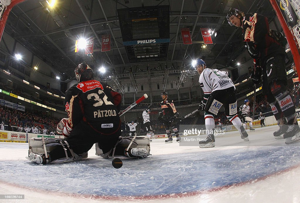 Daryl Boyle (C) of Augsburg watches the puck during the DEL match between Hannover Scorpions and Augsburger Panther at TUI Arena at TUI Arena on January 9, 2013 in Hanover, Germany.