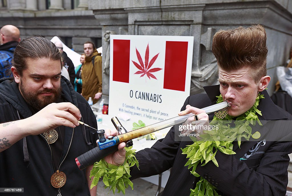 Daryl Brown smokes marijuana from a bong as thousands of enthusiasts gather to celebrate the 19th anniversary of 4/20 April 20, 2014 at the art gallery in downtown Vancouver, British Columbia, Canada. The event, which began in 1995 with a gathering of less than 200 people, has grown into a worldwide celebration.