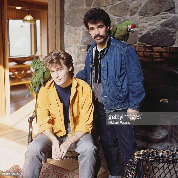 Daryl Hall and John Oates of American pop duo Hall and Oates posing each with a parrot on his shoulder Upstate New York 1983