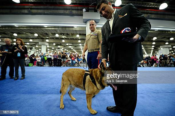 Daryl Hendricks presents the DOGNY Heroic Military Dog Award to Lucca and handler Gunnery Sgt Chris Willingham at Day 1 of AKC 'Meet The Breeds'...