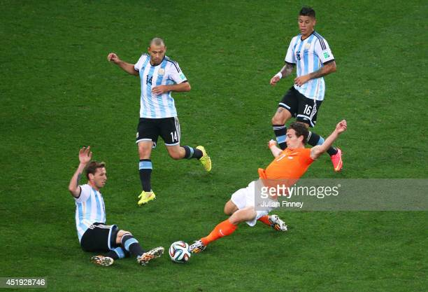 Daryl Janmaat of the Netherlands challenges Lucas Biglia of Argentina during the 2014 FIFA World Cup Brazil Semi Final match between the Netherlands...