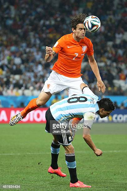 Daryl Janmaat of the Netherlands heads the ball over Enzo Perez of Argentina during the 2014 FIFA World Cup Brazil Semi Final match between...