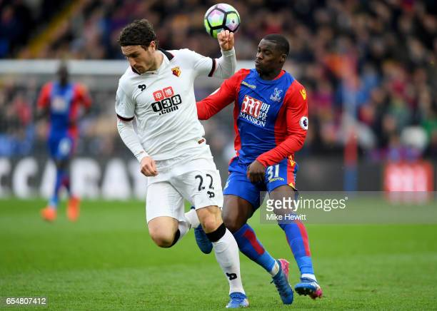 Daryl Janmaat of Watford is put under pressure from Jeffrey Schlupp of Crystal Palace during the Premier League match between Crystal Palace and...