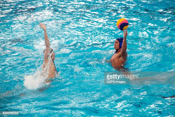 Daryl Khoo Tiong Jin of Malaysia defends against Thailand's Pattanit Chompoosan in the men's water polo round robin match during the South East Asian...