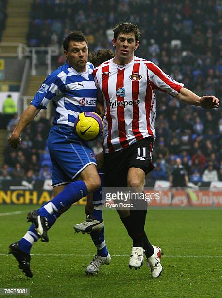 Daryl Murphy of Sunderland tussles with Graeme Murty of Reading during the Barclays Premier League match between Reading and Sunderland at the...