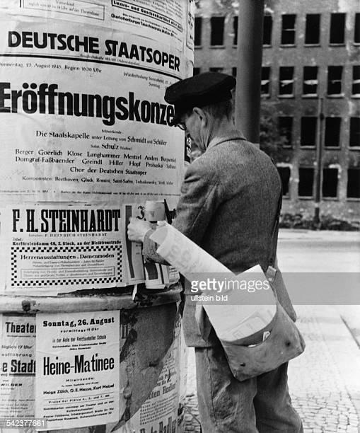 'Das kulturelle Leben regt sich wieder'Plakatkleber vor einer LiftfassSäuleBerlin August 1945FotoFritz Eschen