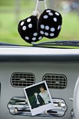 Dash of a car with a picture and hanging fuzzy dice