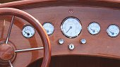A vintage wooden speedboat's dashboard displaying all the controls and the steering wheel